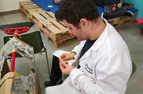 scuola di formazione un ragazzo disabile che usa il collage per costruire una casa di cartone
