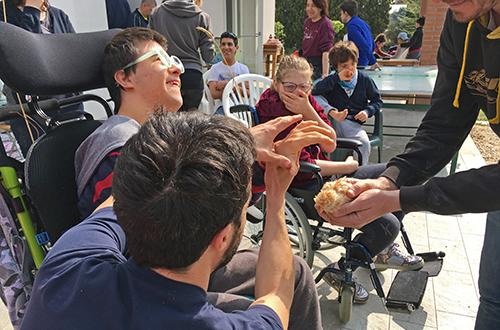 scuola di formazione, ragazzi disabili che usano il tatto per scoprire la morbidezza di un pulcino