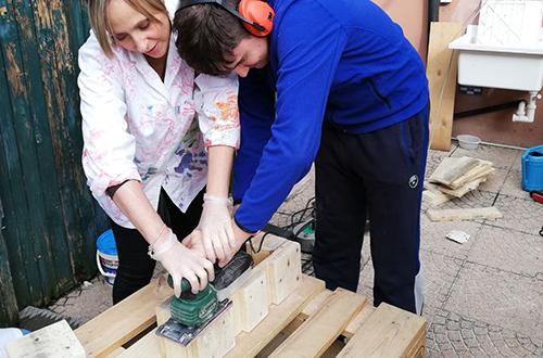 scuola di formazione professionale ragazzo disabile con operatrice che lavorano il legno